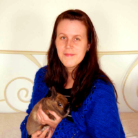 Nainen istuu sohvalla pieni ruskea kani sylissään.