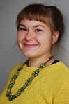 Kuvassa keltaiseen paitaan ja vihertävään helmikoruun pukeutunut hymyilevä nainen. Eläinten viikkoa vietetään joka vuosi sadoissa kouluissa ympäri Suomen.