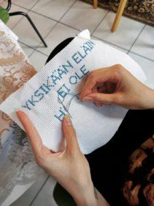 Lähikuva ihmisestä joka tekee ristipistotyötä. Työ on kesken ja siihen on muodostumassa sinisin kirjaimin teksti: Yksikään eläin ei ole häkkieläin. Eläinten viikkoa vietetään joka vuosi sadoissa kouluissa ympäri Suomen.